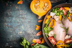 Raw chicken breast in cooking pot with pumpkin and vegetables ingredients on dark rustic background Royalty Free Stock Images