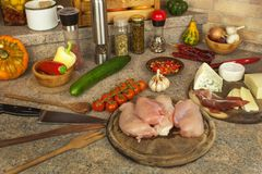 Raw chicken breast fillets on kitchen breadboard. Preparation of home diet meals with vegetables and cheese. Stock Photography