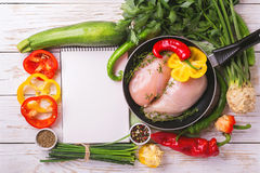 Raw chicken breast fillets with vegetables ingredients in pan Stock Image