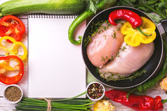 Raw chicken breast fillets with vegetables ingredients in pan Royalty Free Stock Photo