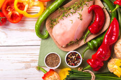 Raw chicken breast fillets with vegetables ingredients in pan Stock Photos