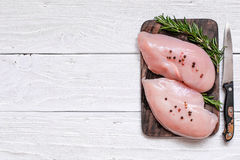 Raw chicken breast fillets on wooden cutting board Royalty Free Stock Photo