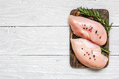 Raw chicken breast fillets on wooden cutting board with herbs and spices. Top view with copy space Royalty Free Stock Images