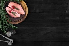 Raw chicken breast fillets on wooden cutting board with herbs and spices. Top view with copy space. Raw chicken breast fillets on wooden cutting board with herbs Royalty Free Stock Image