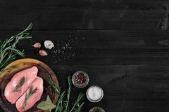 Raw chicken breast fillets on wooden cutting board with herbs and spices. Top view with copy space. Raw chicken breast fillets on wooden cutting board with herbs Stock Photography