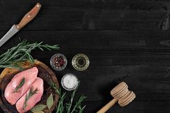 Raw chicken breast fillets on wooden cutting board with herbs and spices. Top view with copy space. Raw chicken breast fillets on wooden cutting board with herbs Royalty Free Stock Images