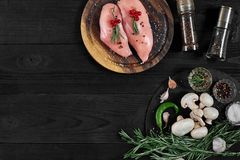 Raw chicken breast fillets on wooden cutting board with herbs and spices. Top view with copy space. Raw chicken breast fillets on wooden cutting board with herbs Royalty Free Stock Photography