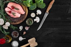 Raw chicken breast fillets on wooden cutting board with herbs, spices and vegetables. Top view with copy space. Raw chicken breast fillets on wooden cutting Royalty Free Stock Photos
