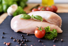 Raw chicken breast on a slate plate. With fresh cherry tomatoes, garlic and herbs. Cooking ingredients, healthy eating Stock Photo