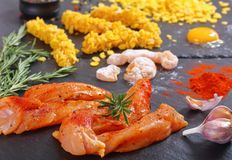 Raw chicken breast strips on black stone plate. With corn flakes, egg yolk, rosemary and spices, view from above, close-up Stock Images