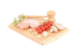 Raw chicken breast and vegetables with meat mallet Stock Image