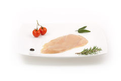 Raw chicken breast on white dish with herbs Stock Images