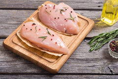 Raw chicken breasts. And spices on  cutting board Royalty Free Stock Photo