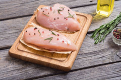Raw chicken breasts. And spices on  cutting board Stock Photography
