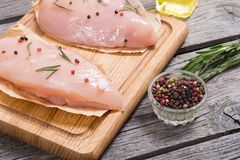 Raw chicken breasts. And spices on  cutting board Stock Photos