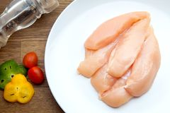 Raw chicken breasts and spices on white plate.  Stock Photo