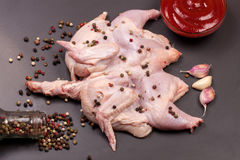 Raw chicken carcass with peppercorns on a dark background Stock Image