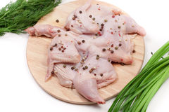 Raw chicken carcass with peppercorns and greenery on the cutting board isolated on white background.  Stock Images