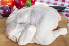 Raw chicken close up. Raw chicken on wooden board with knife and vegetables Stock Photo
