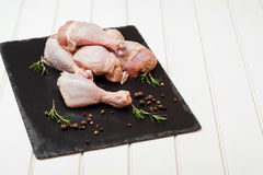 Raw chicken drumstick on black slate with salt, garlic, rosemary, spices. Raw chicken drumstick on a black slate with salt, garlic, rosemary, spices Royalty Free Stock Images