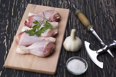 Raw chicken drumstick on board with salt, garlic and ax. Raw chicken drumstick on the board with salt, garlic, ax on wooden table Stock Photos
