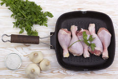 Raw chicken drumstick in pan with salt, garlic, parsley. On wooden table Royalty Free Stock Photo