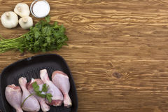 Raw chicken drumstick in pan with salt, garlic, parsley. On wooden table Stock Photos