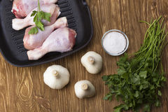 Raw chicken drumstick in pan with salt, garlic, parsley. On wooden table Stock Images