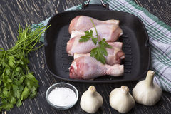 Raw chicken drumstick in pan with salt, garlic, parsley. On wooden table Stock Image