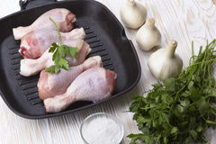 Raw chicken drumstick in pan with salt, garlic, parsley Stock Images