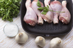 Raw chicken drumstick in pan with salt, garlic, parsley Royalty Free Stock Photo
