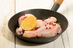Raw chicken drumstick with red peppercorn, lemon slice and rosem. Ary in a pan on white rustic table Stock Photography