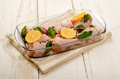 Raw chicken drumstick with sage and lemon in a glass bowl. Raw chicken drumstick with sage and lemon slice in a glass bowl Royalty Free Stock Photos