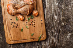 Raw chicken drumstick on wooden board with salt, garlic, rosemary, spices. Raw chicken drumstick on a wooden board with salt, garlic, rosemary, spices Stock Photography