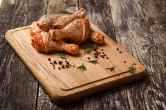 Raw chicken drumstick on wooden board with salt, garlic, rosemary, spices. Raw chicken drumstick on a wooden board with salt, garlic, rosemary, spices Stock Image