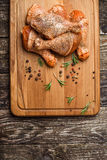 Raw chicken drumstick on wooden board with salt, garlic, rosemary, spices. Raw chicken drumstick on a wooden board with salt, garlic, rosemary, spices Stock Images