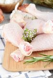 Raw chicken drumsticks. On board Stock Photography
