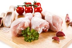 Raw chicken drumsticks on cutting board. On white background Stock Photo