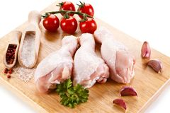Raw chicken drumsticks on cutting board. On white background Stock Image