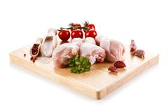 Raw chicken drumsticks on cutting board. On white background Stock Photos