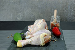 Raw chicken drumsticks. On a gray stone with copy space Stock Images