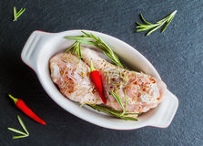 Raw chicken drumsticks with spices in oval baking dish on black stone board, top view. Ready to roast or bake Royalty Free Stock Photo