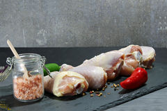 Raw chicken drumsticks. With spices, peppers and olive oil and himalayan salt on a grey stone Royalty Free Stock Photos