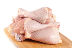 Raw chicken drumsticks on a wooden cutting boardn white background.  stock image