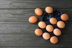 Raw chicken eggs in ceramic holder. On wooden background, top view. Space for text royalty free stock images