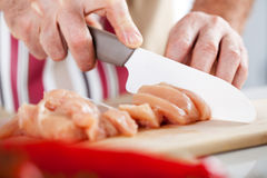 Raw Chicken filet. Senior Male Hands Cutting Chicken filet on the kitchen board royalty free stock photography