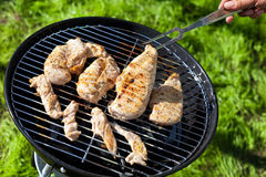 Raw chicken fillet breast cooking on barbeque grid Stock Images