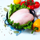 Raw chicken fillet in a cast iron frying pan with vegetables on a table, isolated on white. Selective focus. Copy space Royalty Free Stock Photography