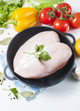 Raw chicken fillet in a cast iron frying pan with vegetables on a table, isolated on white. Selective focus. Copy space Royalty Free Stock Photos