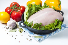 Raw chicken fillet in a cast iron frying pan with vegetables on a table, isolated on white. Selective focus. Copy space Stock Photography